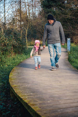holding hands while walking: Man and little girl holding hands while walking over a wooden pathway into the forest
