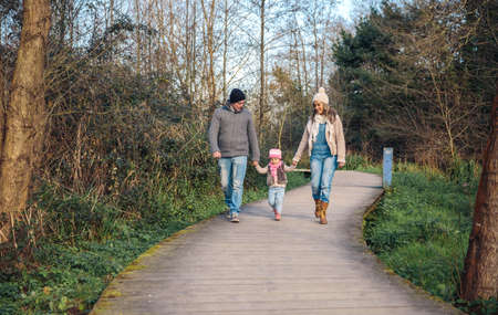 holding hands while walking: Family holding hands while walking over a wooden pathway into the forest Stock Photo