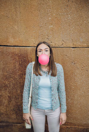 brunette girl: Portrait of beautiful young brunette teenage girl blowing pink bubble gum over a stone wall background