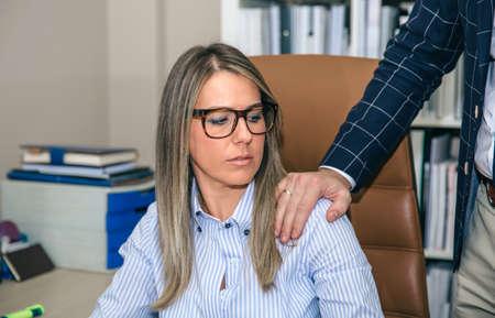 Boss Putting Hand über die Schulter der blonden Sekretärin im Büro. Sexuelle Belästigung am Arbeitsplatz Konzept.