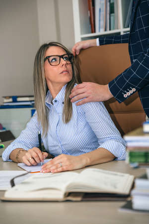 Porträt schockiert blonde Sekretärin suchen, um Chef der Hand über ihre Schulter im Büro setzen. Sexuelle Belästigung am Arbeitsplatz Konzept. Standard-Bild