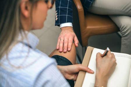 上司オフィスでブロンド秘書の足を置く手のクローズ アップ。仕事の概念でのセクシュアル ・ ハラスメント。 写真素材
