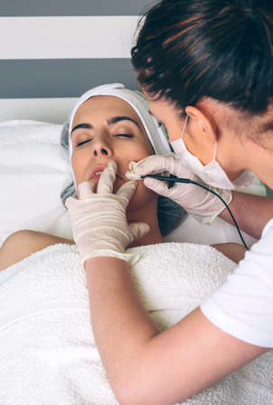 rf: Young pretty woman getting rf lifting treatment on clinical center. Medicine, healthcare and beauty concept.