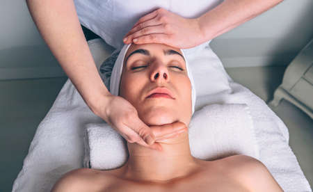 lymphatic drainage therapy: Close up of young woman with closed eyes receiving facial massage on a clinical center. Medicine, healthcare and beauty concept. Stock Photo
