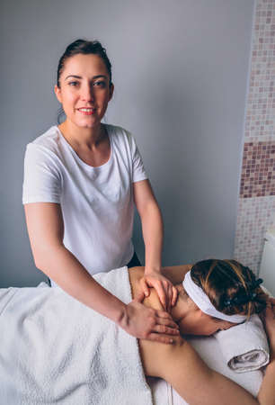 Portrait of smiling female massage therapist doing relaxing massage on shoulders of young woman in a clinical center. Medicine, healthcare and beauty concept.