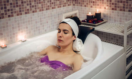 beauty eyes: Beautiful woman with closed eyes lying in tub doing hydrotherapy treatment. Health and beauty concept.