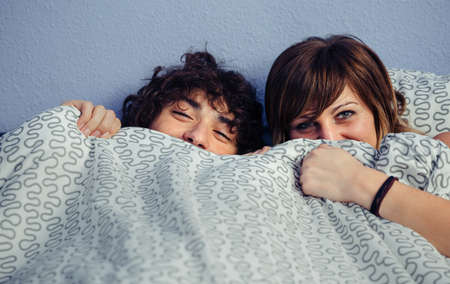 bedcover: Happy couple laughing and covering mouths under duvet