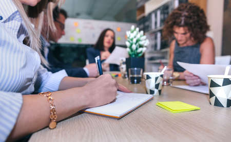 work table: Woman writing notes in a meeting with teamwork