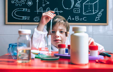 formula one: Kid playing with chemical liquids over table