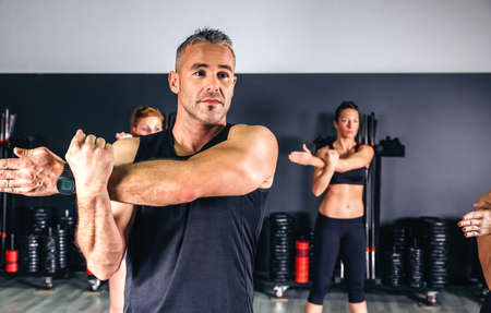 Man stretching his arms in fitness class photo