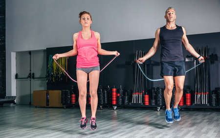 Young couple doing exercises with jumping ropes photo