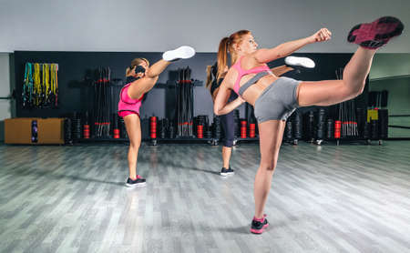 Women in a boxing class training high kick photo