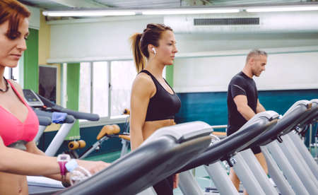 Woman with earphones training over a treadmill photo