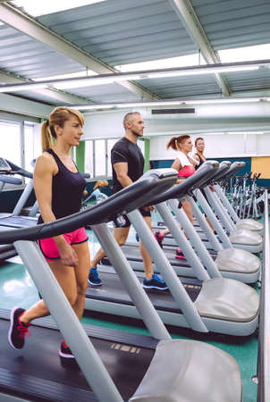 People training over treadmills on fitness center photo