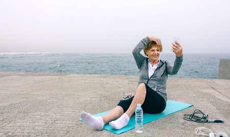 Senior sportswoman taking selfie by sea pier