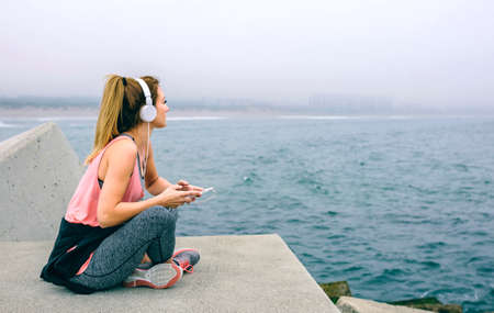 Sitting sportswoman with headphones watching the sea Stock Photo