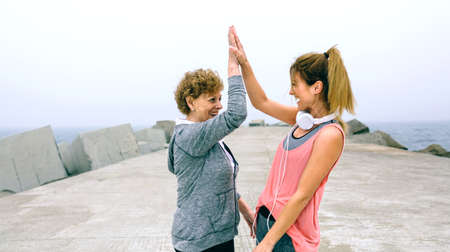 Senior sportswoman and female friend high five by sea pier Stock Photo - 84014762