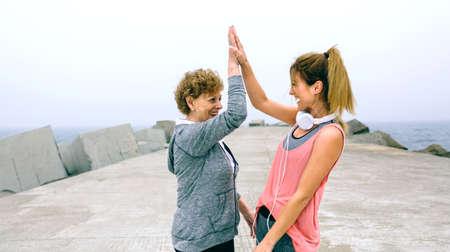 Senior sportvrouw en vrouwelijke vriend hoog vijf bij zeepier