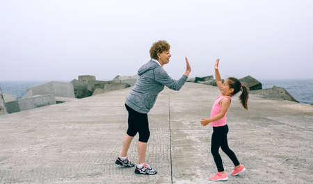 Senior sportswoman and little girl high five by sea pier Stock Photo