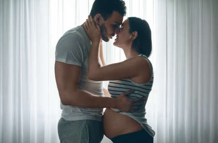 Man embracing and kissing his pregnant woman Stock Photo - 84649533