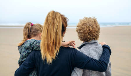 three generations: Back view of three generations female looking at sea on the beach in autumn Stock Photo