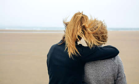 Back view of senior and young woman looking at sea on the beach in autumn Stockfoto