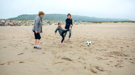 three generations: Three generations female playing soccer on the beach in autumn Stock Photo