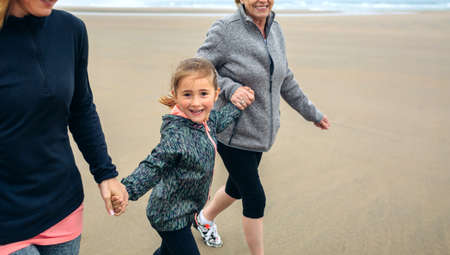 three generations: Girl running with two women on the beach in autumn