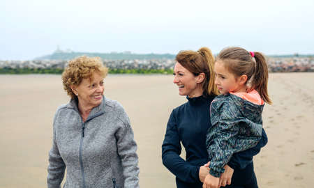 three generations: Three generations female walking on the beach in autumn Stock Photo