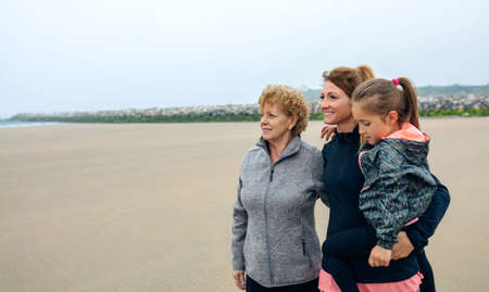 three generations: Three generations female looking at sea on the beach in autumn Stock Photo