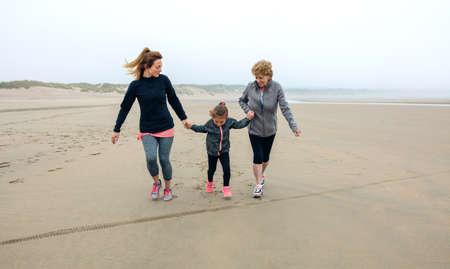 Three generations female running on the beach in autumn Stock Photo