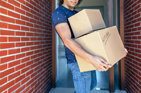 company: Young man carrying moving cardboard boxes