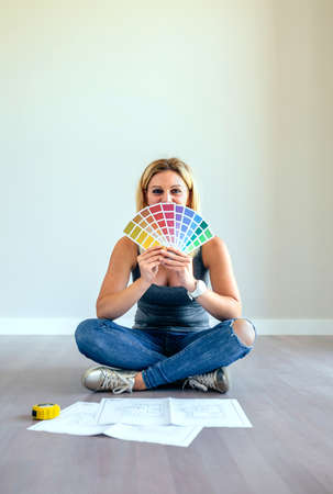Young woman with color chart sitting in a empty living room Stock Photo