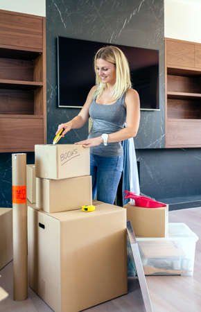 Woman unpacking moving boxes in her new home