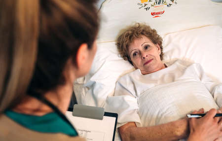 Young female doctor comforting older female patient Stock Photo