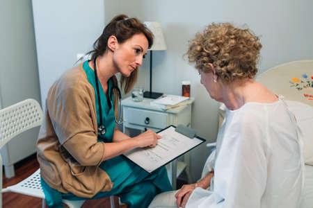 Vrouwelijke arts die een vragenlijst invult aan een hogere patiënt