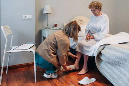 Female carer wearing slippers to elderly female patient