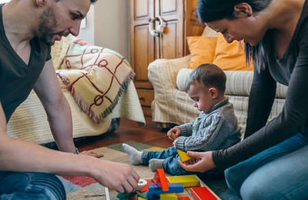 Young parents playing with their toddler son a wooden game building in the living room