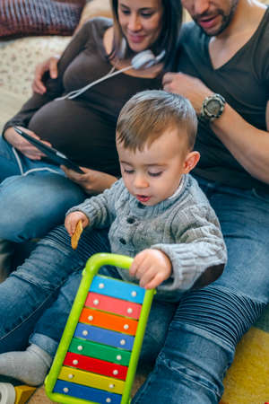 Pregnant woman and her husband looking at the tablet while their little son plays Stock Photo