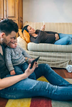 Young father looking at the tablet with his little son while the pregnant mother looks the mobile. Focus on pregnant woman in background