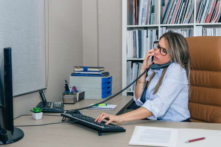 Portrait of busy businesswoman talking simultaniously on cell and stationary phone Фото со стока - 94046239
