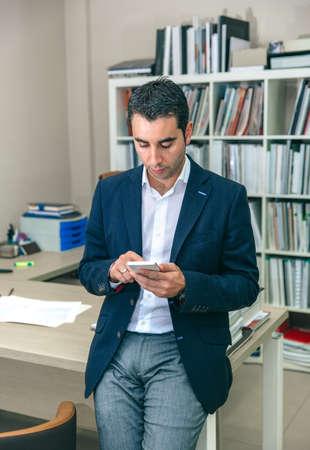Portrait of handsome businessman looking smartphone sitting over office table Foto de archivo
