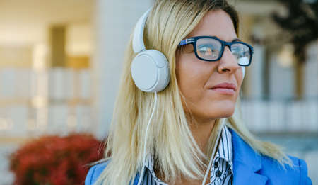 Closeup of businesswoman with formal clothes, nose piercing and headphones Stock Photo