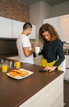 Curly woman ready to go out looking smartphone while having fast breakfast in home with young man