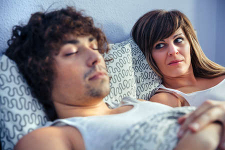 Frustrated and angry woman looking to young man sleeping in bed. Couple relationship and problems concept.