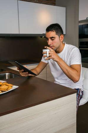 台所で朝食を食べ、タブレットを見ている若い男 写真素材 - 96174031
