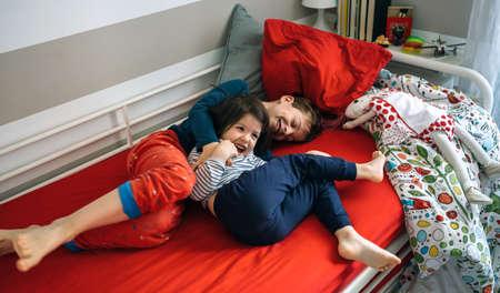 Hermano y hermana, cosquillas y riendo mientras está acostado en la cama