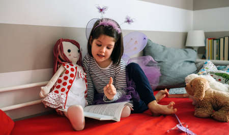 Little girl disguised as a butterfly sitting on the bed reading a book to her rag doll Stock fotó