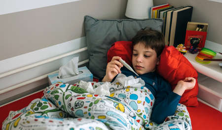 Cold child lying on the bed looking at the thermometer