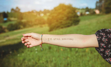 Closeup of female arm with the text -Im still waiting- written in the skin over a nature background